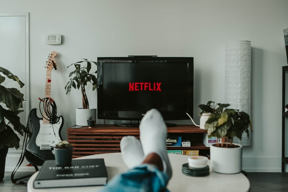 man looking at television with Netflix